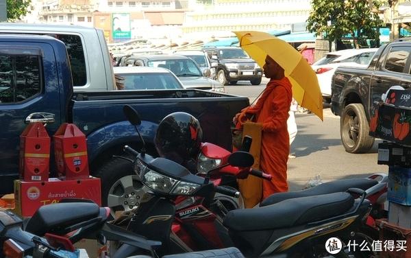 ▲在金边你会看见,穿着人字拖,打着太阳伞,骑着摩托的僧人