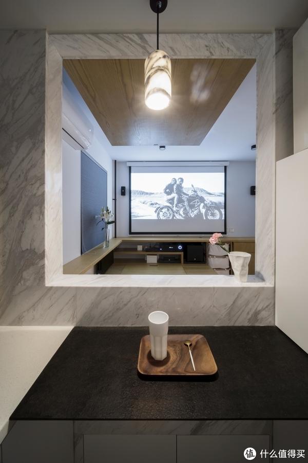 ▲可以看到黑色台面下方的白色柜门,打开之后是榻内的空间,为加强厨房小吧台的氛围感,上方吊线灯采用3000k色温光源,材质也是与墙面一致的大理石