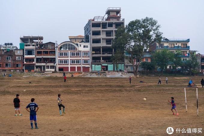 一旁踢足球的少年