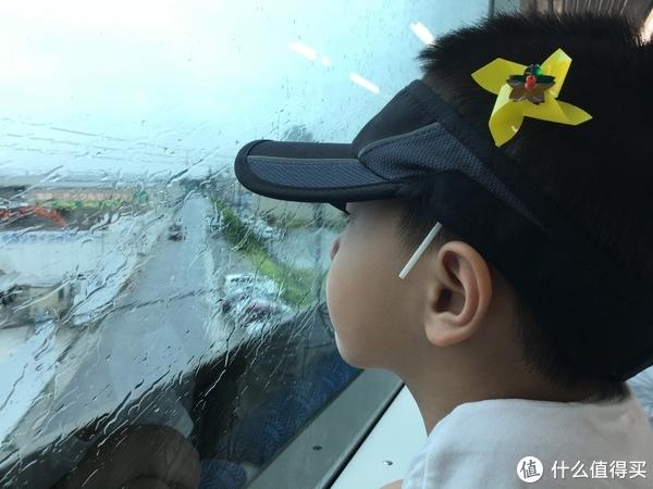 依旧下着雨,小宝有点忧伤的看着车窗外,帽子上别着的小风车,是前一晚酒店送给小朋友的礼物。