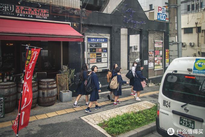 车上的游客和街道上的学生们打招呼