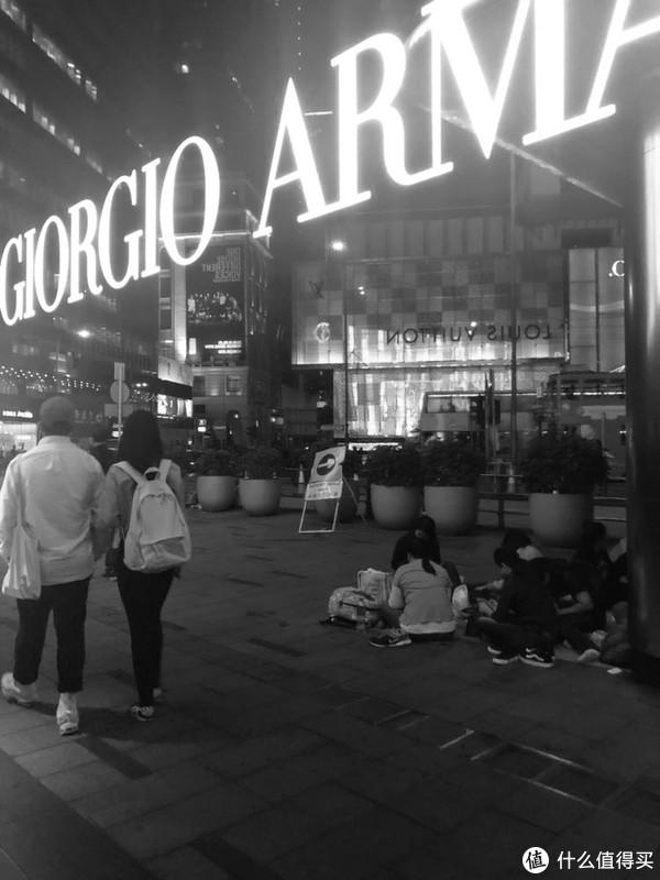 大牌店面的镜面、游客和聚会的人们