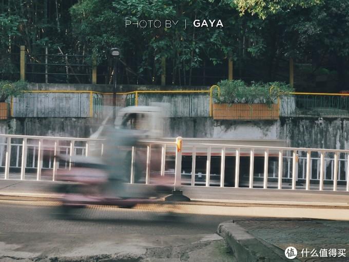 """这张照片是快门速度降低后静止拍摄的,如果镜头跟着电动车走,就变成了""""摇拍""""。"""