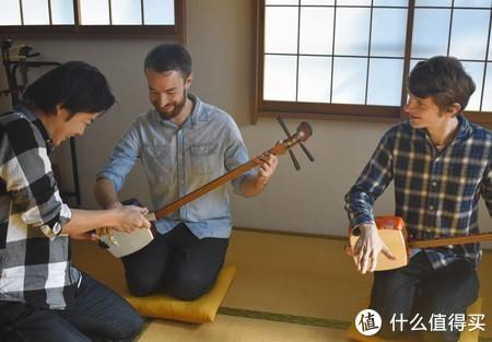 向仓桥胜学习三味线弹奏方法的瑞德(中)和穆勒根