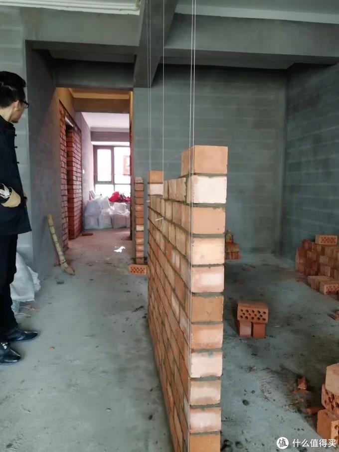 施工的第一步往往就是敲墙与砌墙