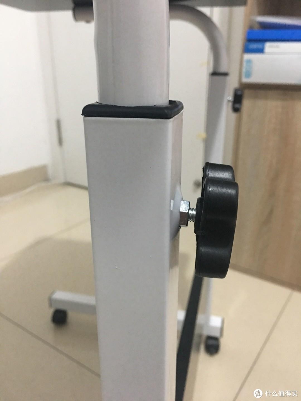 调节桌子的高低部位,黑色的旋钮按钮是松紧作用