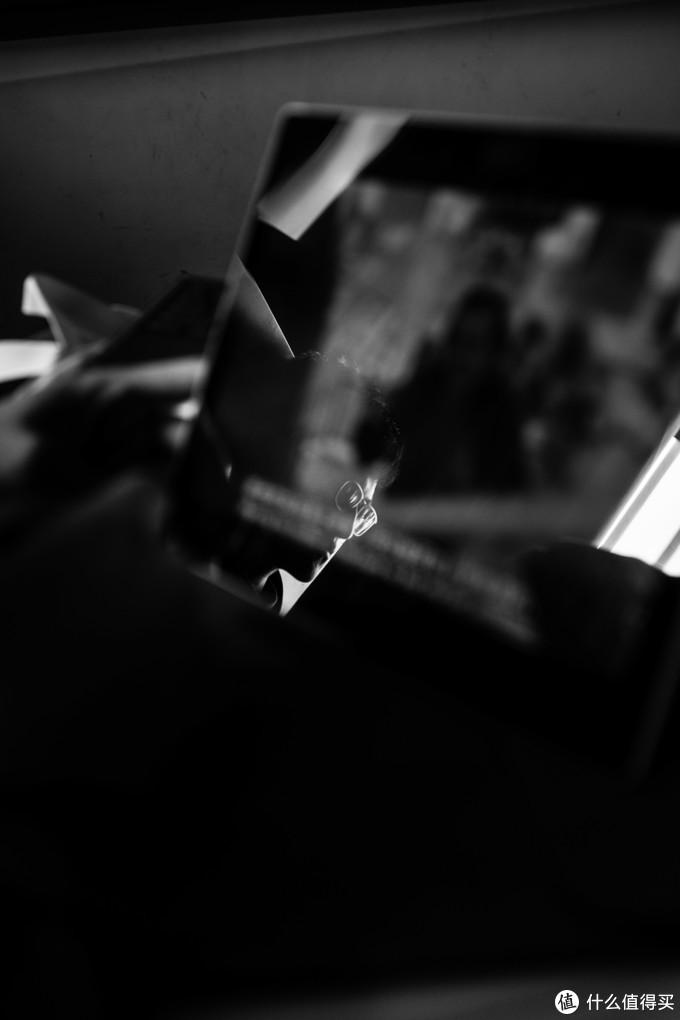 同学冷峻的脸庞反射在平板电脑的屏幕上,平板上是库布里克的《闪灵》中女主在楼梯用榔头击晕杰克尼尔克森的桥段