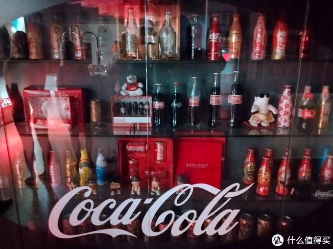 各种各样的包装,上面有可口可乐早期的玻璃瓶包装,最早的可乐是在药店售卖的,玻璃瓶也像药瓶一样。