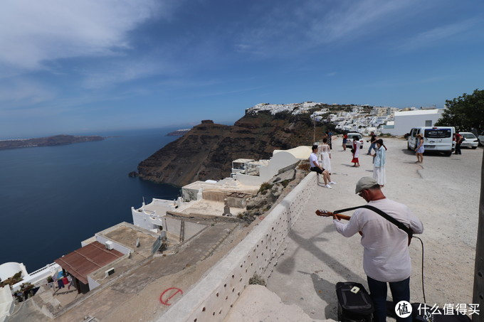 卖唱的艺人和教堂上方空地拍蓝顶的游人们