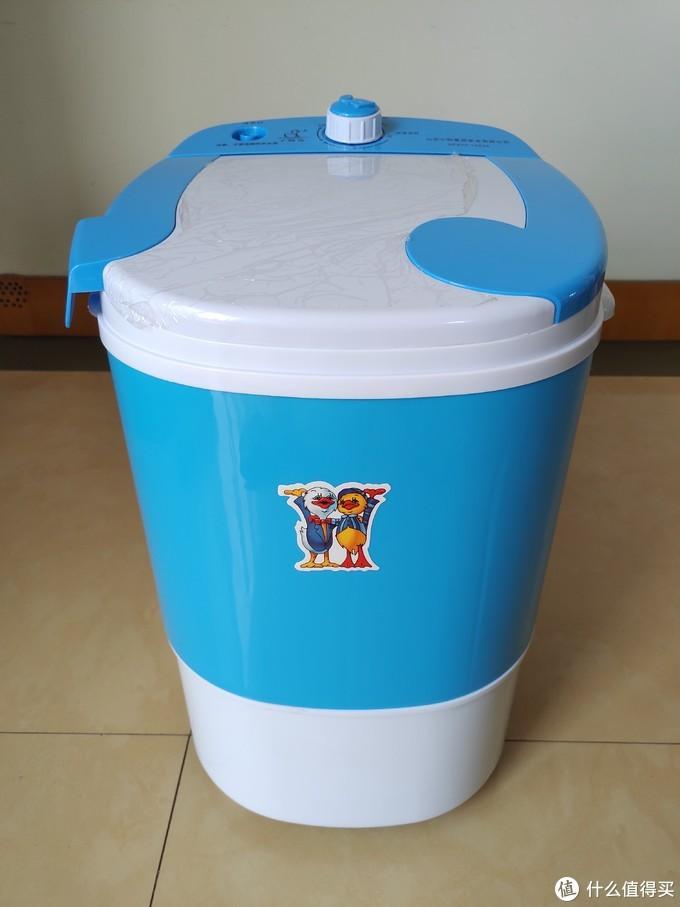 洗衣机整体为塑料材质,蓝白配色,顶部为进水和操控区域,带有一个盖板。桶体上半部蓝色部分为洗衣桶,下半部白色部分为电机仓。正面两只小鸭的贴纸画风非常有年代感。