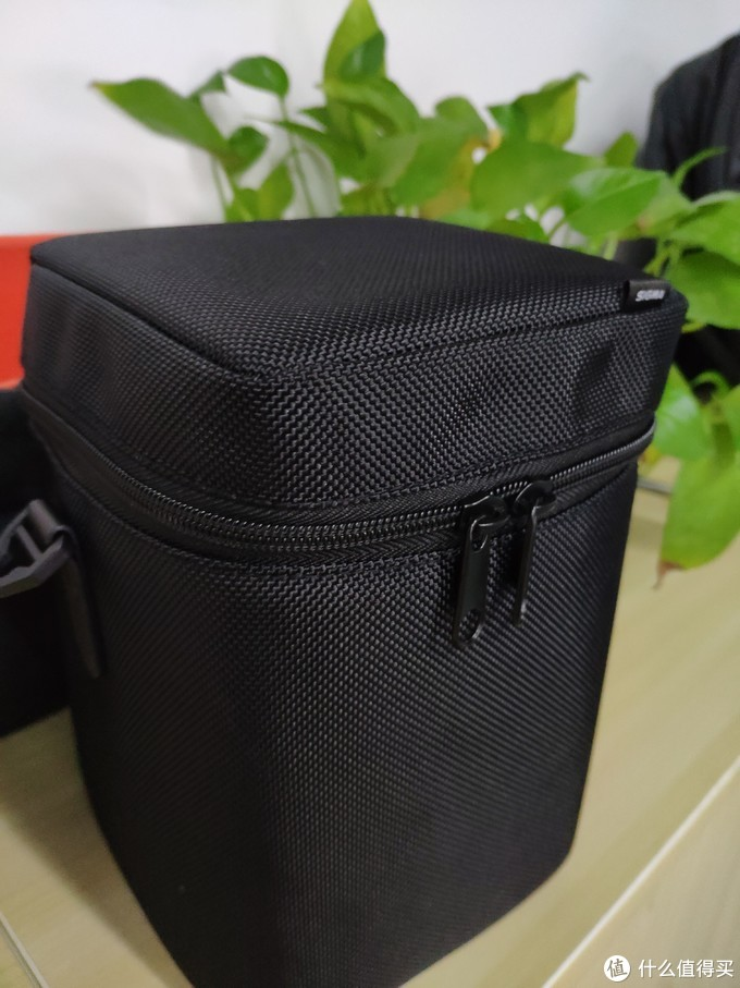 硕大的黑色包,注意镜头最好倒着放进去,上部有海绵凹槽保护卡口位置
