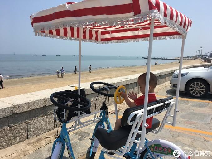 坐在自行车上狂涂防晒的小孩子,预防衰老,从小做起
