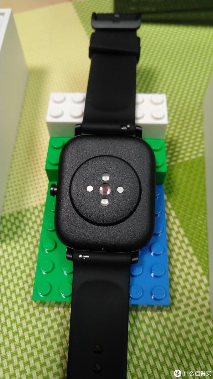 边框是磨砂金属,背面是颗粒塑料,横向两颗圆点是磁吸充电触点,竖向的是心率监测