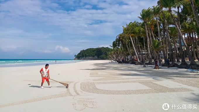 酒店工作人员用耙子在沙滩做出酒店名字