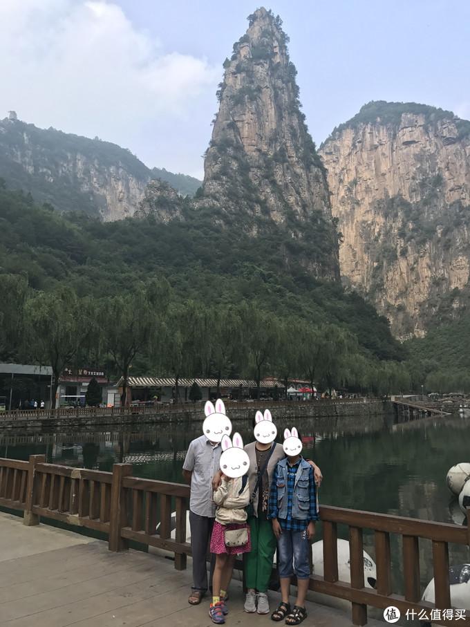 父母和孩子在红豆峡标志性主峰下合影
