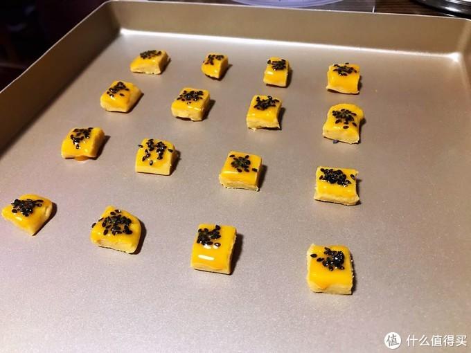 接着压扁切块,每个上面涂蛋黄液撒上芝麻