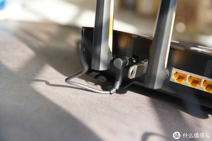 另一侧,L形的电源接头很容易就把路由器给顶起来了,往两侧倾斜又会和天线或USB冲突