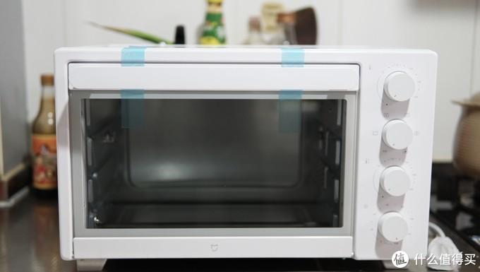 烤箱是通身小米白,右侧的旋钮也是很简单易懂,箱门和插线都用胶带粘着;
