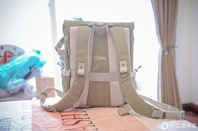 背后,填充物比较饱满,肩带也比较厚实,背着舒适度不错。背部有条绷带,可以挂行李箱。