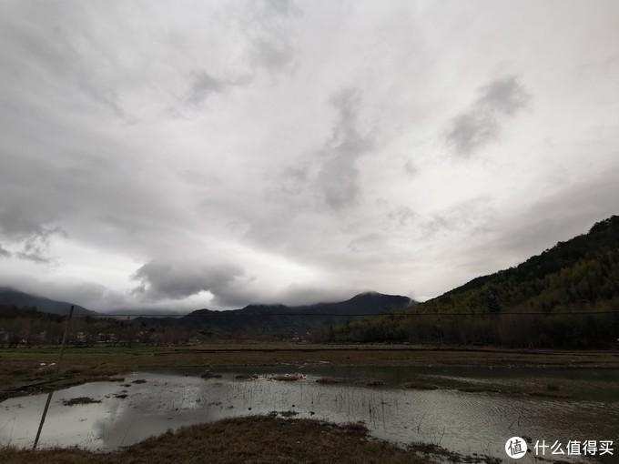 酒店去宏村的路上,一个池塘,远处黄山山脉,以及慢慢放晴的天空