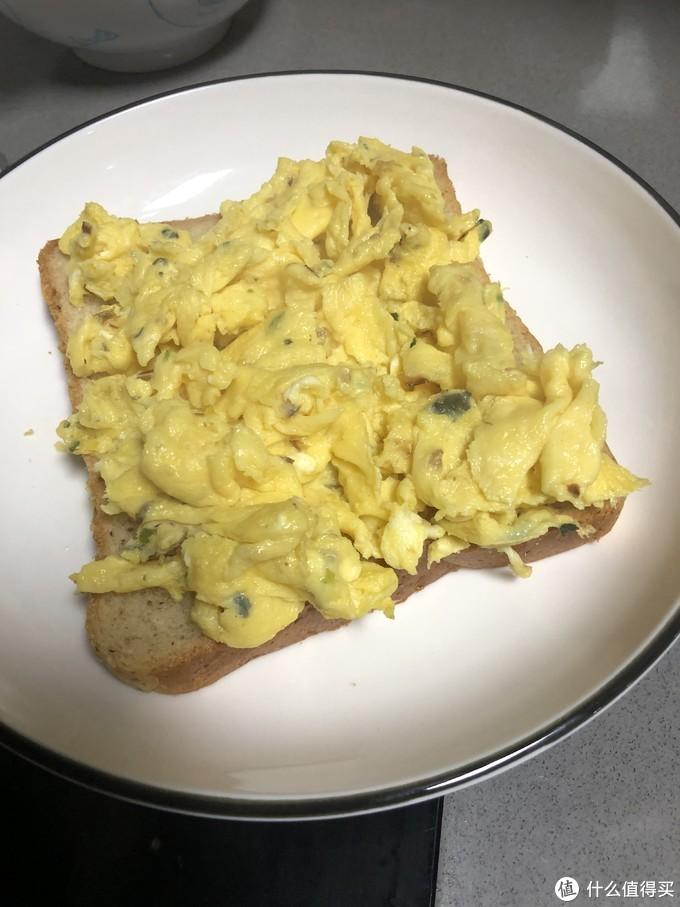 将刚刚炒好的鸡蛋放在面包上,鸡蛋炒到刚刚凝固就行,后面还要加热