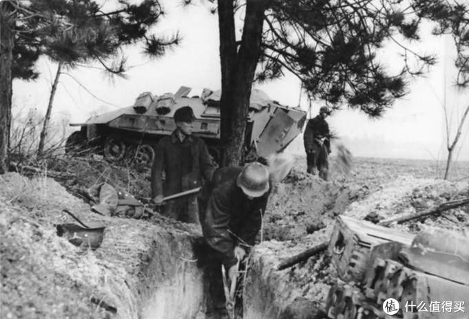 正在挖掘战壕的德军士兵与人民冲锋队队员,背景处为一辆Sd.kfz. 251装甲车。1945年,德国境内