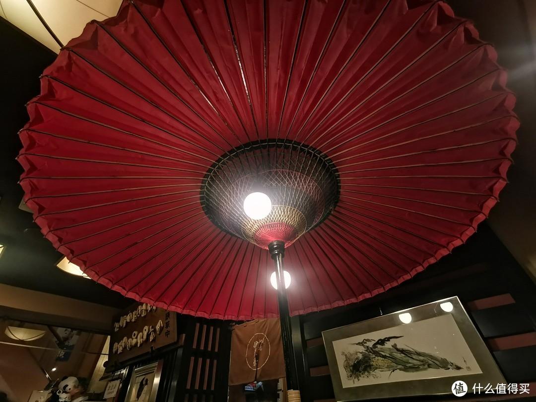 榻榻米上面是一个红色的纸伞