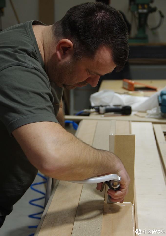 工匠为带有沟槽的板材涂胶