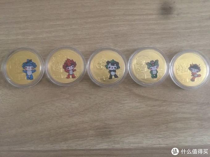 正面是奥运会的五个吉祥物和中国的五种名花,以及中国建筑传统装饰元素。五枚纪念币都用塑料保护壳装着