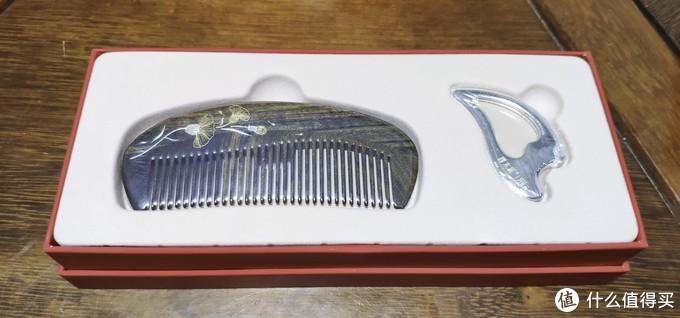 盒子中有两件物品,一件是来自谭木匠的天然木护发梳,以及一件来自一帧的纯银按摩板。