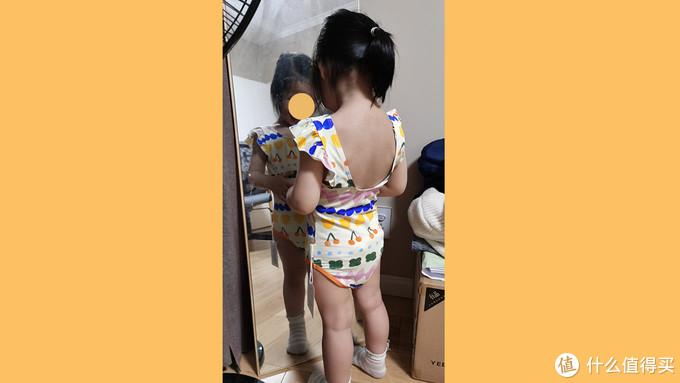 女儿穿上泳衣对着镜子感觉很满意