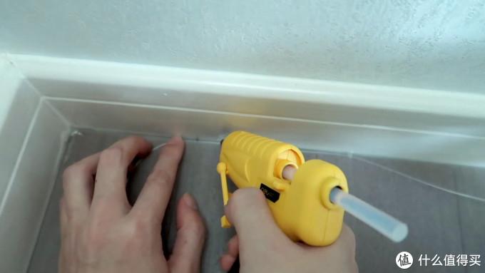 用热熔胶枪将隐形光纤沿着墙固定