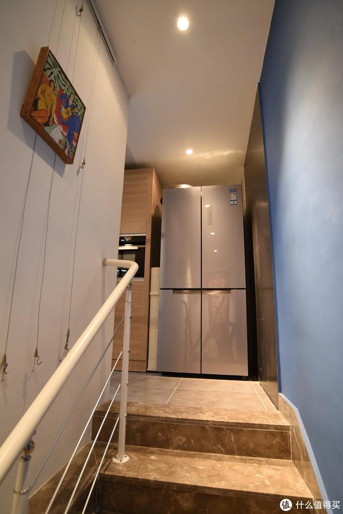 冰箱整体还是比较大气,预留位置还有空间,左侧用了超窄收纳柜,装一点饮料听方便,右侧放置了伸缩楼梯,方便更换一下楼梯上方的挂画、换换灯泡什么的