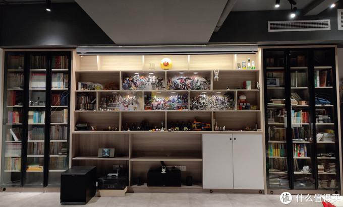 另一个书架主要是用来展示模玩的,兼顾一些影音功能,比如摆放幕布、功放、中置音箱等。