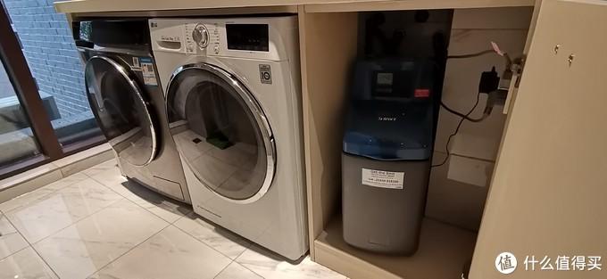 软水机装在阳台的柜子里, 和洗衣机、烘干机并排装到一起,柜子没有装背板,净深大约59厘米,装这个软水机非常合适
