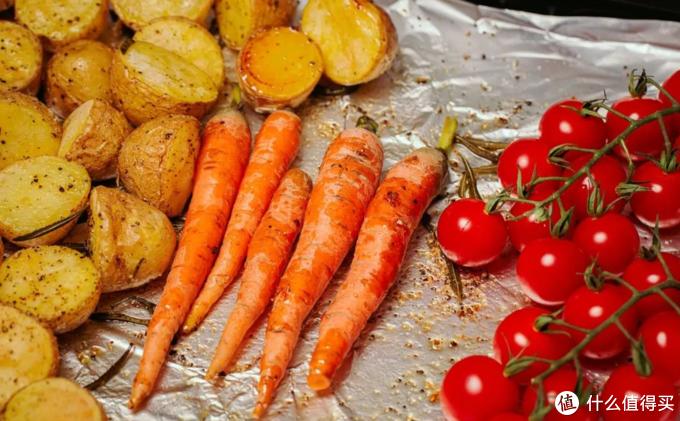 取出烤盘将土豆移动一旁,放入小胡萝卜和番茄,继续烘烤约二十分钟。