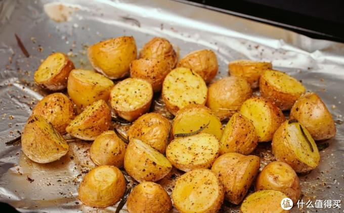 换烤盘垫铝箔纸,放入对半切开的小土豆和收集的羊油,再加适量橄榄油、海盐、黑胡椒和迷迭香,放入烤箱中层 200 度左右烘烤半小时,烤好后取出备用。