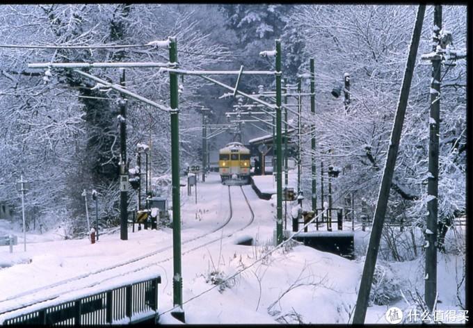 冬日里白雪覆盖的车站中准备出发的电车
