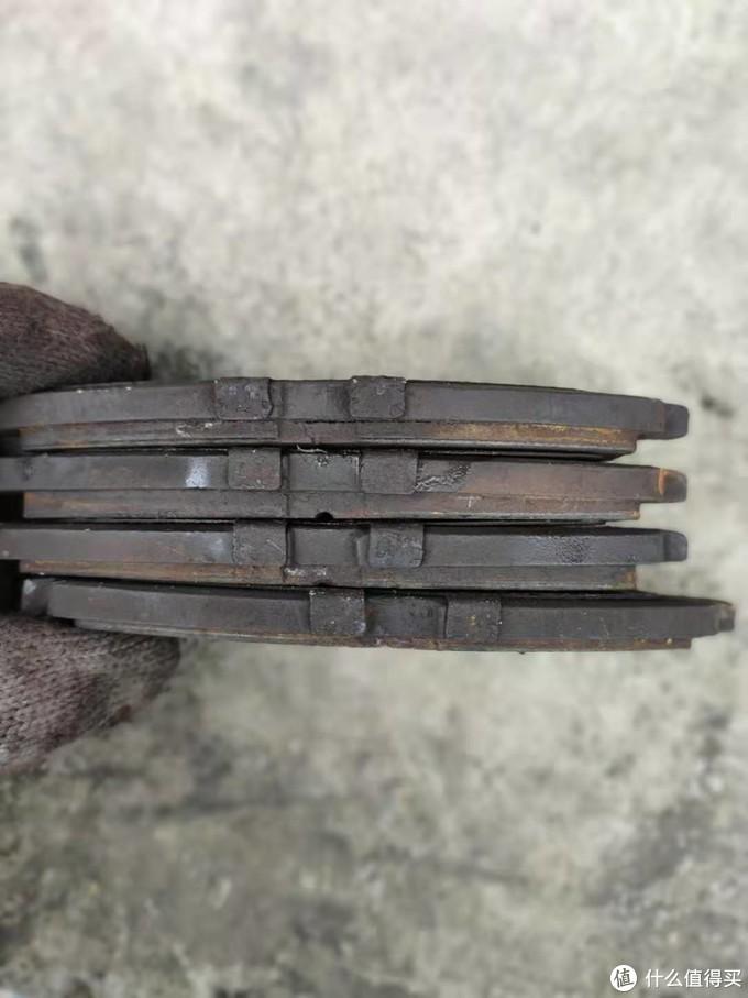 拆下来的四片刹车片,明显有一片偏磨很严重,这就是那个卡钳的回位销回位不正常导致的。