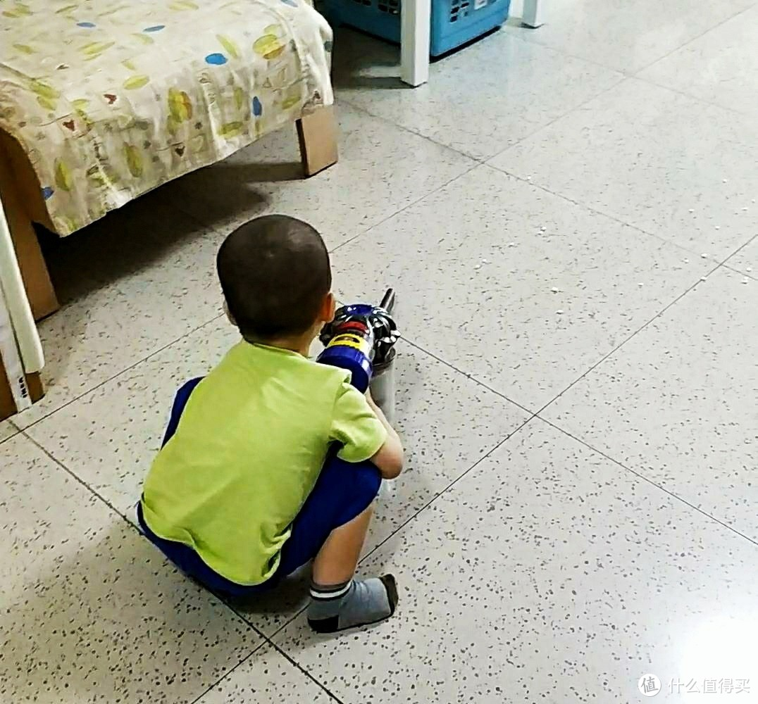 正在用戴森吸尘器吸抽纸渣渣的小朋友