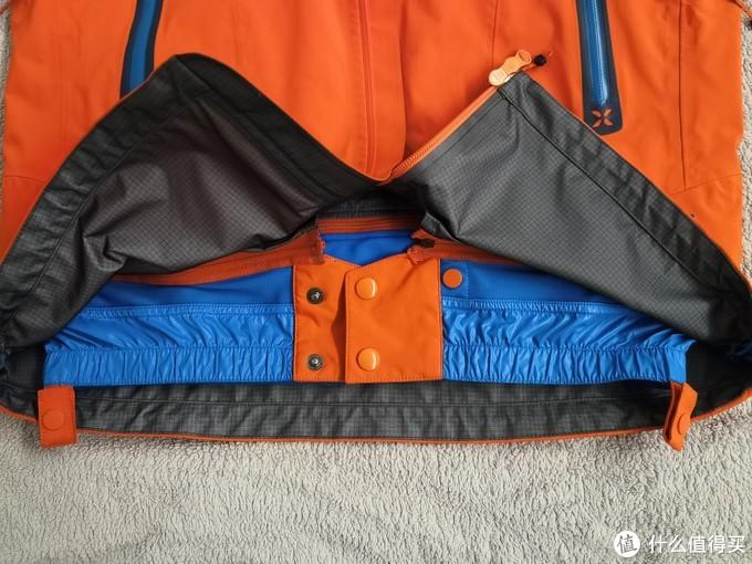 雪裙,通过拉链和外壳链接,可以根据不同的使用要求拆卸,做一些腾挪动作时紧贴住身体,防止风雪倒灌,两侧扣条是配套固定冲锋裤的,加固防倒灌