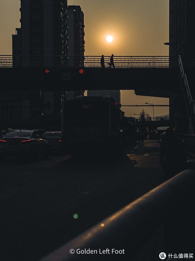 夕阳下,路人从天桥路过。12 PRO MAX