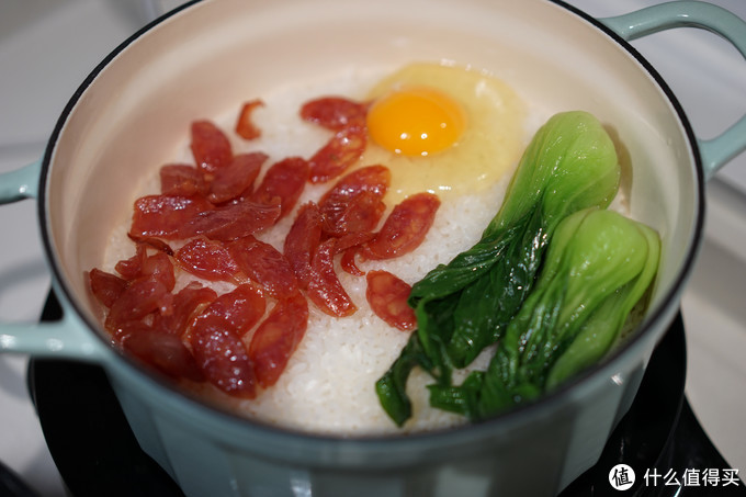 这些步骤操作完煲仔饭的饭也差不多熟了,把菜和蛋放进锅内,倒入料汁,盖上盖子端上饭桌,锅的余温会把蛋加热半熟