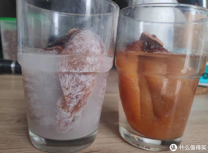 """静置3个小时后,左侧广西柿饼水依然浑浊,而且柿饼上的""""白霜''还在。 右侧的富平柿饼糖霜完全融化,水依然透明"""