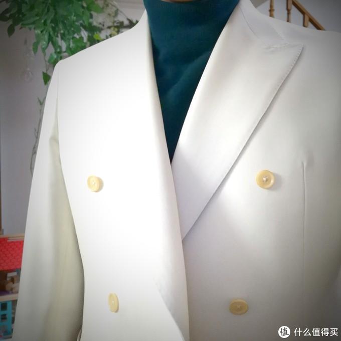 搭配墨绿色针织衫,半高领的简洁领口中和了繁复的戗驳领