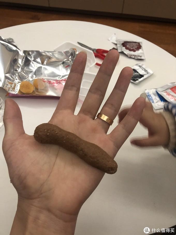 和匀之后拿出来用手再搓几下,平均分成两个球,放置在包装纸上备用,巧克力的面粉搓成长条之后是不是有点埋汰呢,😄