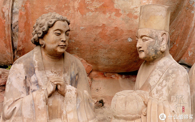 在佛陀眼下立着两位有明显的世俗特征的人