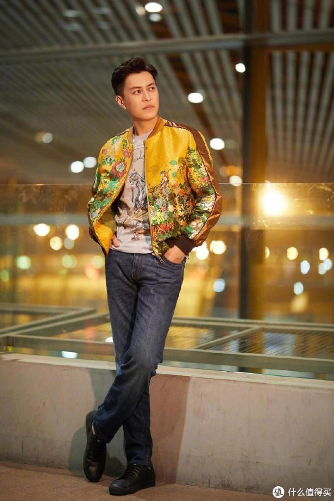 靳东身穿黄色提花夹克,搭配鲜艳的花朵和怪人,内搭灰色印花T恤与经典水洗牛仔裤