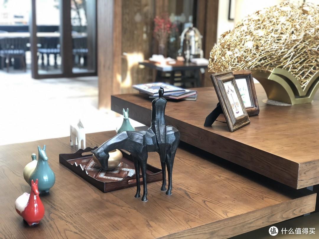 正门的桌子上有着许多的摆件,如书、画框表的画、还有各式以马的形象设计的工艺品,对应这里的茶马古道