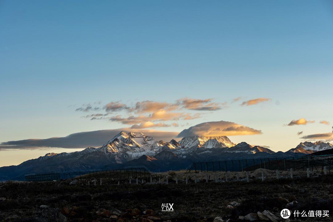 背后就是机场跑道和梅里雪山。山峰上笼罩着帽子云。